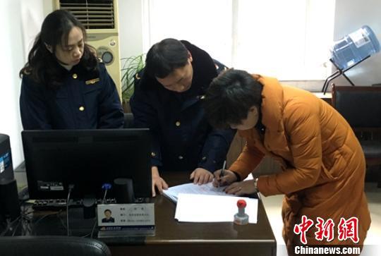 当事人签收工商执法人员送达的处罚决定书。四川工商提供
