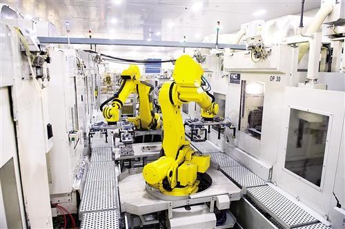 1月16日,机器人在瑞安市瑞明集团智能化托盘线上搬运物料。该生产线上,1个工人可操纵4台机器人,轻松完成相当于以前30个工人的工作。 新华社记者 翁忻�D摄