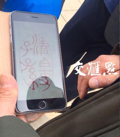 """濮存昕向记者展示刻有祖训的""""清白吏子孙""""的家传印章。"""
