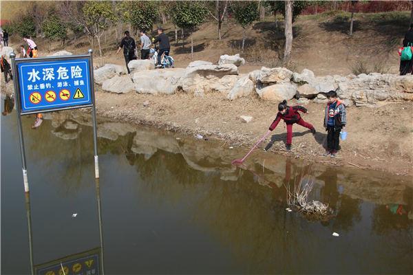 周口公园人工湖引游客踏春 市民无视警示牌玩水