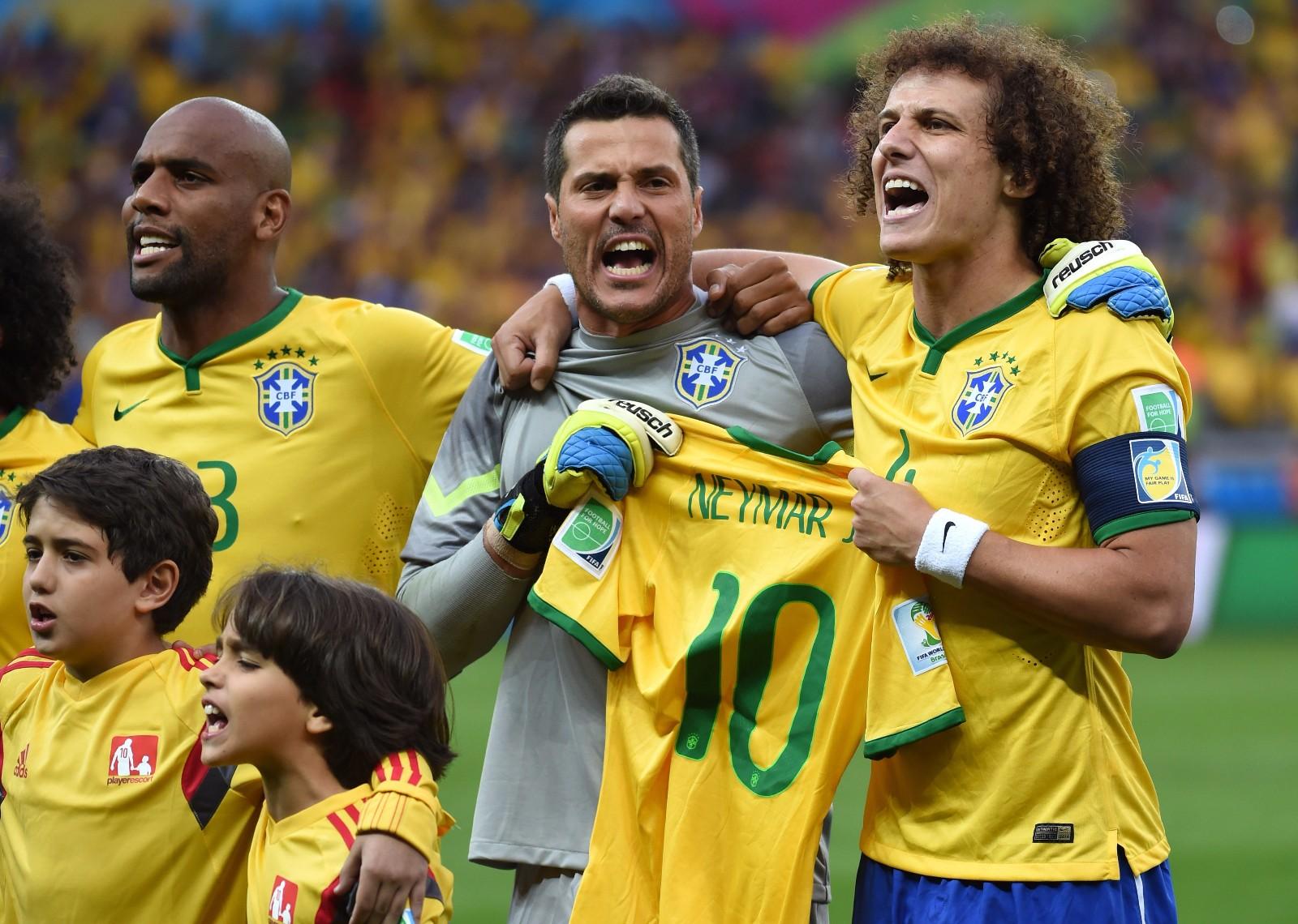 2014年巴西世界杯,巴西国家英雄内马尔在比赛中意外受伤退出世界杯,为了鼓舞球队士气,也为了给伤病中的内马尔加油,在半决赛比赛开始前,队长大卫·路易斯(右)和守门员塞萨尔(中)共同手持内马尔的球衣在开赛仪式上唱国歌(2014年7月8日摄)。