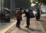 郑州一女环卫工将早餐让失目乞者 失目者跪地致谢