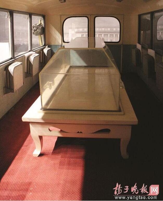 """据周恩来纪念馆工作人员介绍,周恩来灵车的原型是解放牌""""670""""型客车,长8.65米、宽2.54米、高2.95米,自重5吨。该车1976年交付八宝山殡仪馆,加配白色灵床,玻璃棺罩,供重大丧事活动专用。灵车现在的样子,是按1976年1月11日送周总理时的情形装饰的。图为周恩来总理的灵车内部装饰。"""