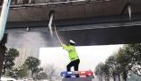 网友发布暖心照片点赞德清交警:站车顶高举竹竿清除冰锥 车还移动着
