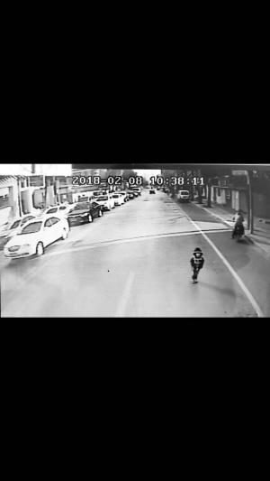 小女孩溜出家门走在马路上。(视频截图)