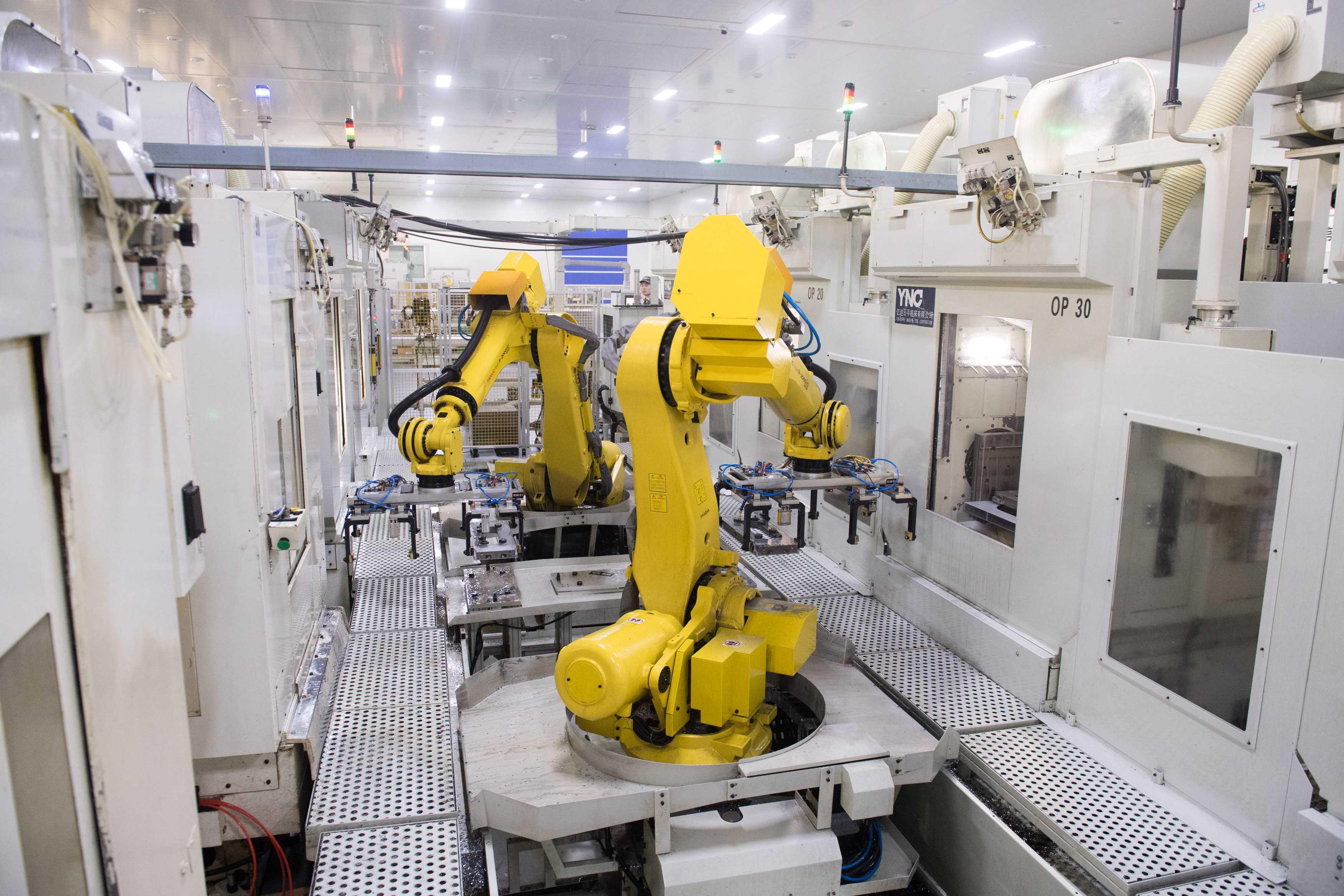 在这条生产线上,1个工人可操纵4台机器人,轻松完成相当于以前30个工人图片