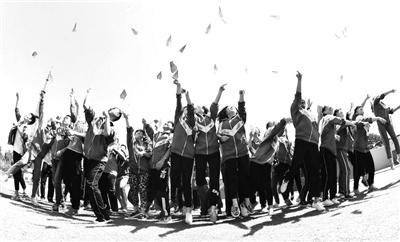 2018年某地高三学生在高考动员会上,把纸飞机掷向天空,放飞梦想。新华社供图